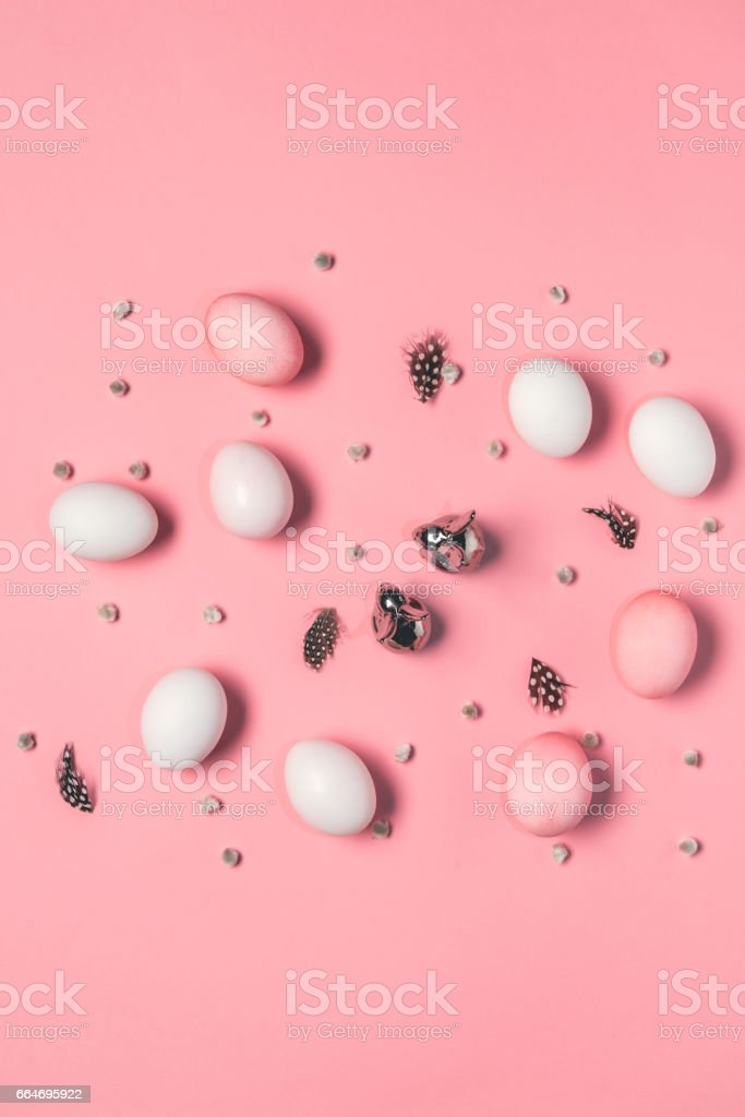 top view of pink and white eggs with bunnies, catkins and feathers on pink. Happy Easter concept stock photo