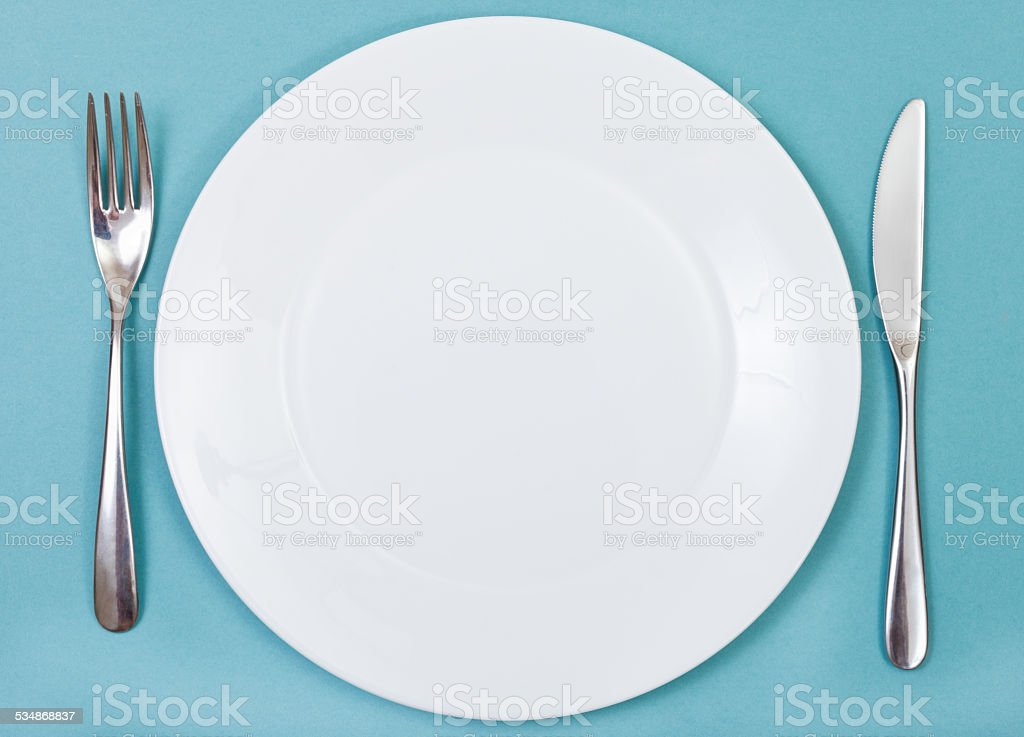 top view of porcelain plate, fork, knife on green stock photo