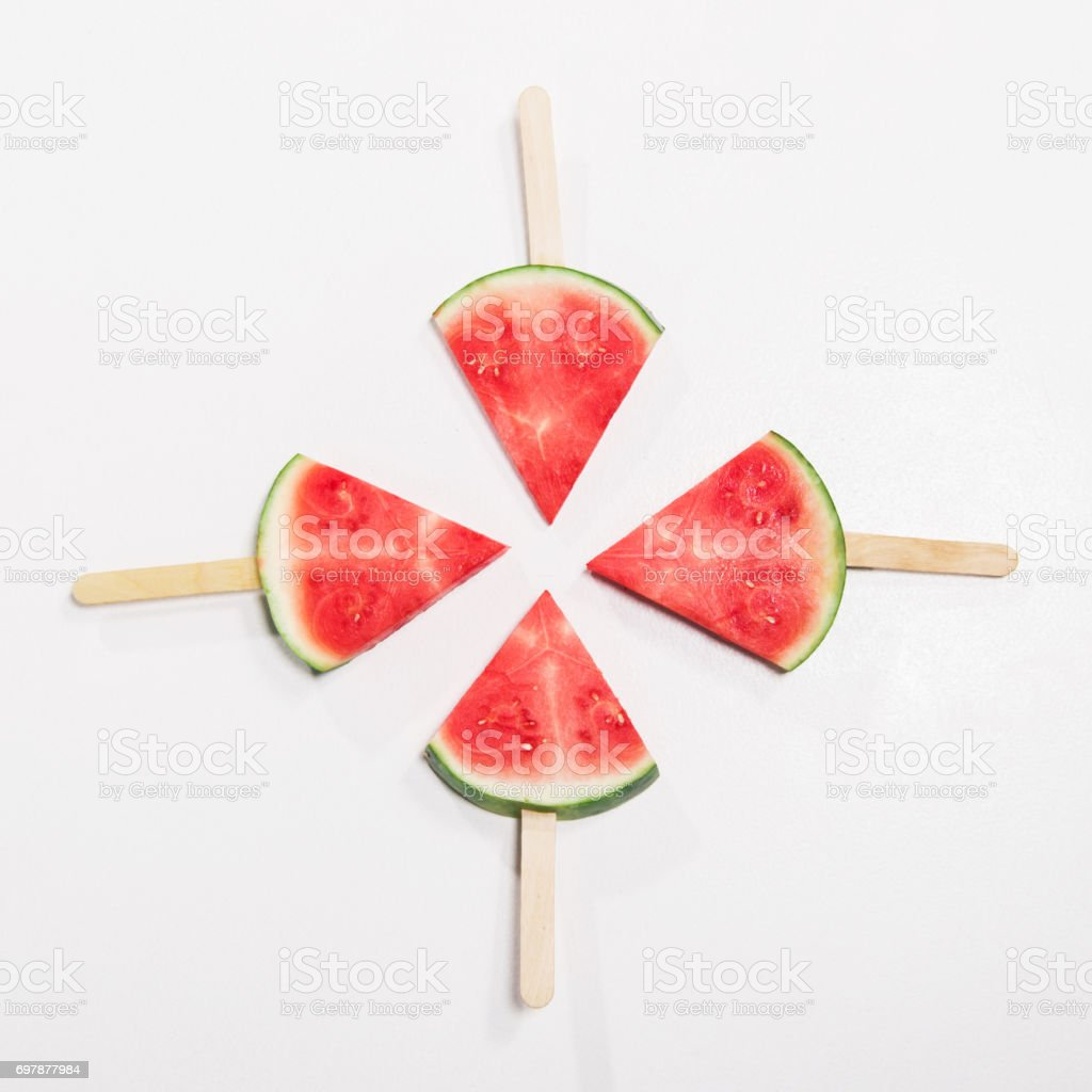 top view of ripe watermelon slices on wooden popsicle sticks stock photo