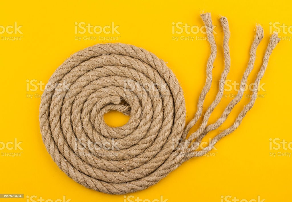 top view of rope spiral with unraveled end yellow background stock photo