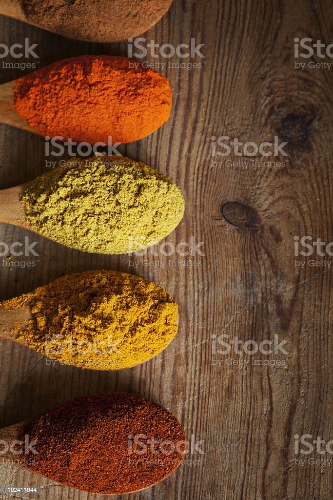 Top view of spices on spoons set on a wooden table stock photo