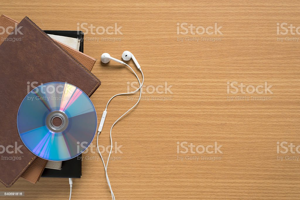 top view of stack of notebook with earphone and dvd dish stock photo