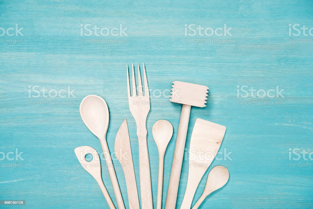 top view of various wooden cooking utensils on blue tabletop stock photo