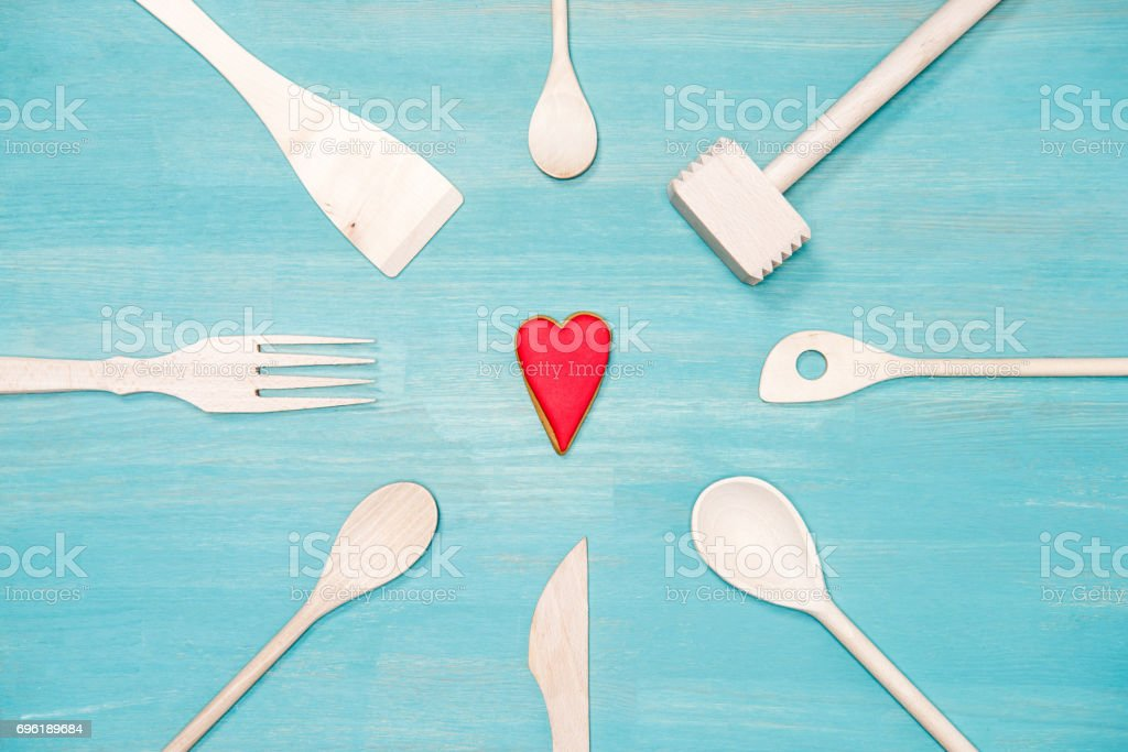 top view of various wooden cooking utensils with heart symbol on blue tabletop stock photo