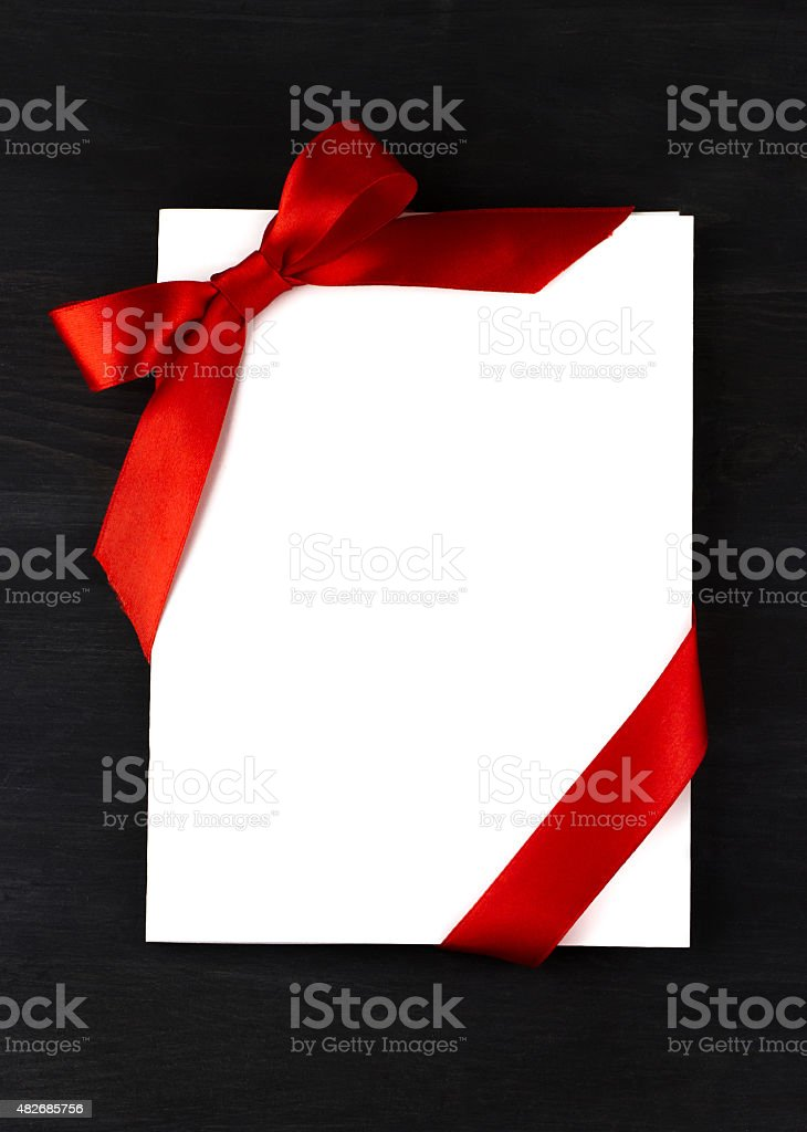 Top view of white holidays gift card with red bow stock photo