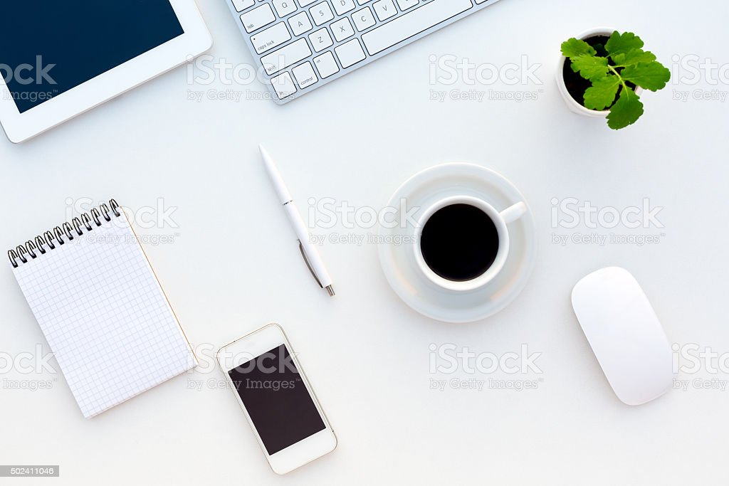 Top View of White Office Desk Modern Electronics Stationery Flower stock photo