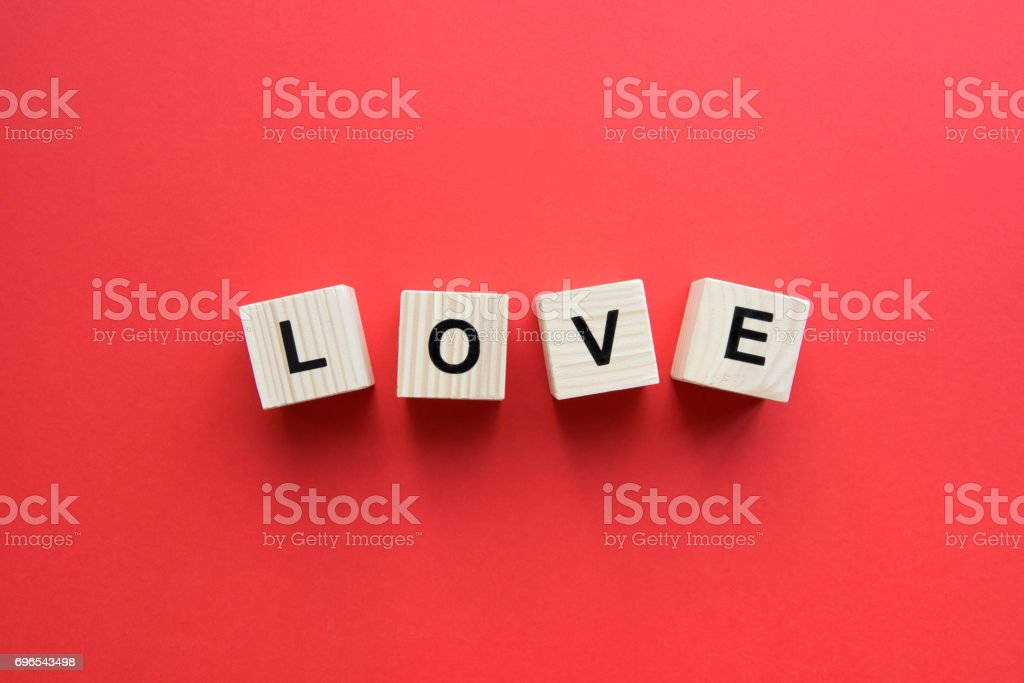 Top view of wooden cubes with love sign on red background stock photo