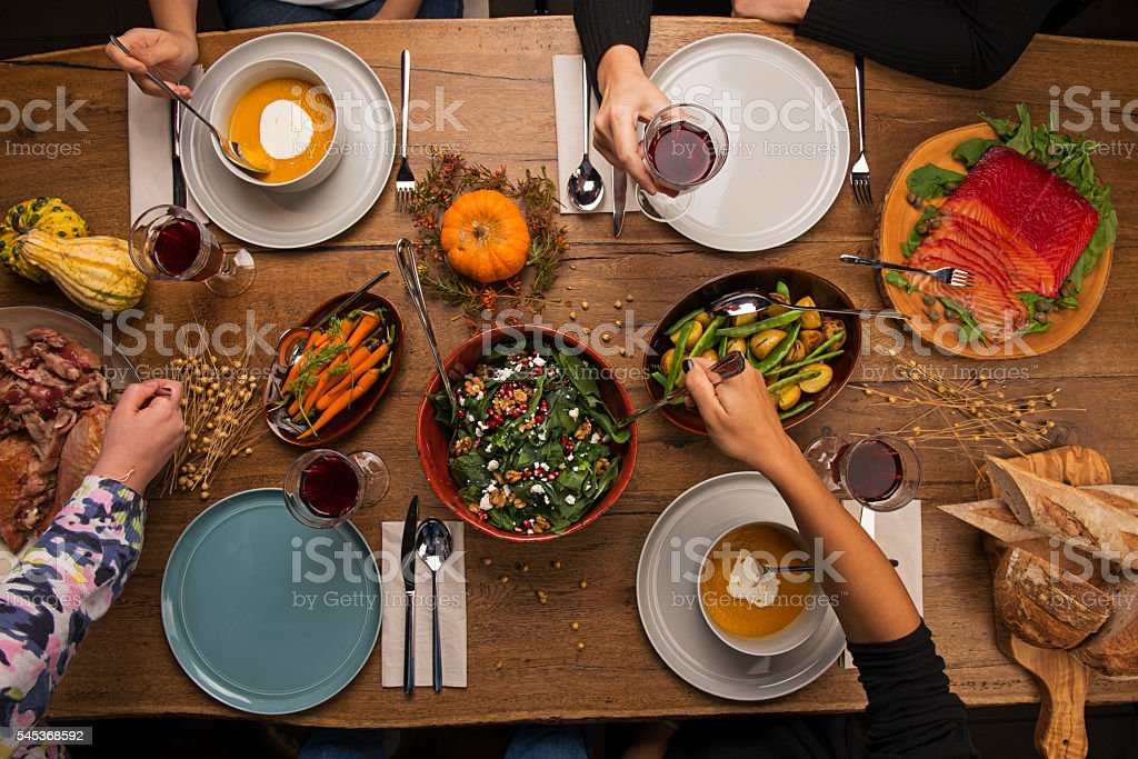 Top view of wooden dinner table and hands serving food stock photo