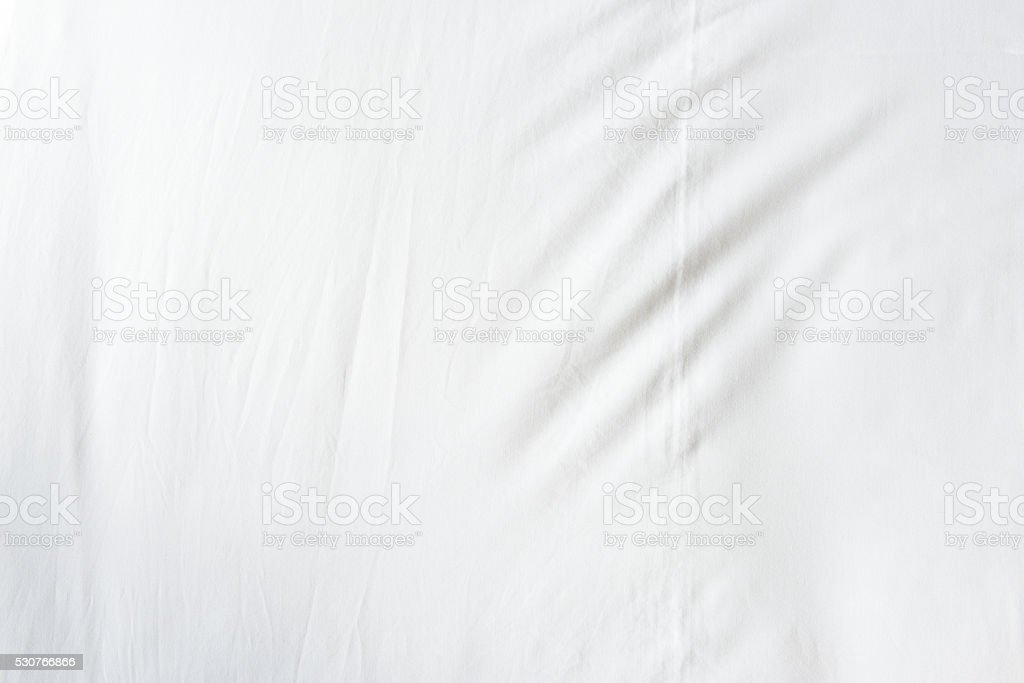 Top view of wrinkles on an unmade bed sheet after a long night sleep...
