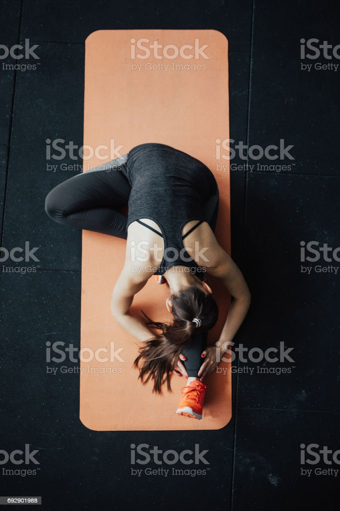 Top view of yoga woman in head-to-knee forward bend pose stock photo