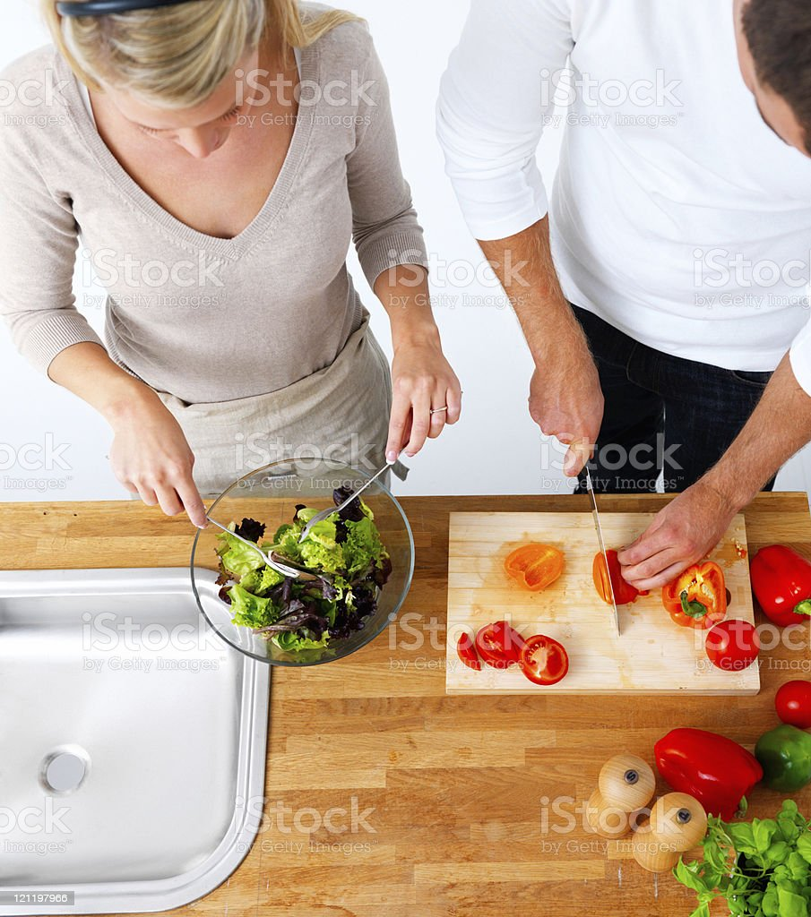 Top view of young couple preparing salad in kitchen royalty-free stock photo