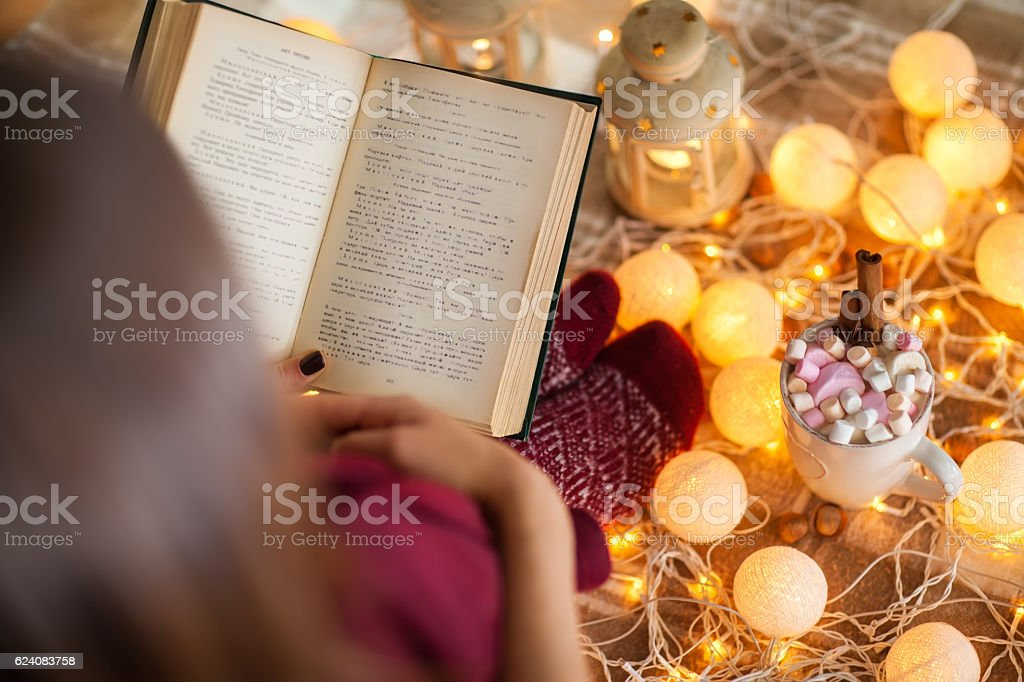Top view of young woman at home reading book stock photo