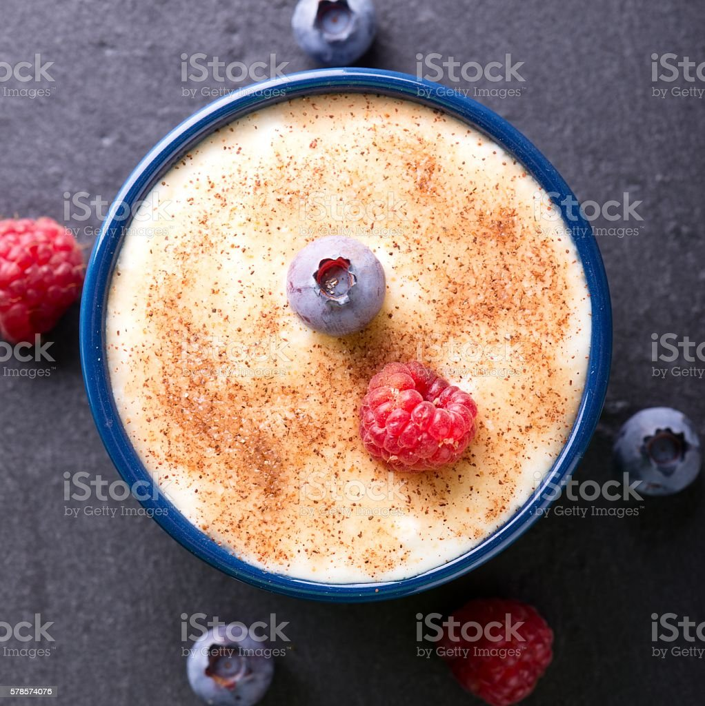Top view on creamy dessert with cinnamon and summer berries stock photo