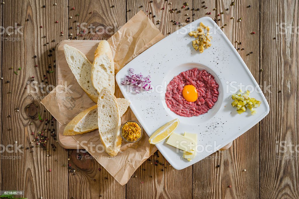 Top view on meat tartare with egg and bread. stock photo