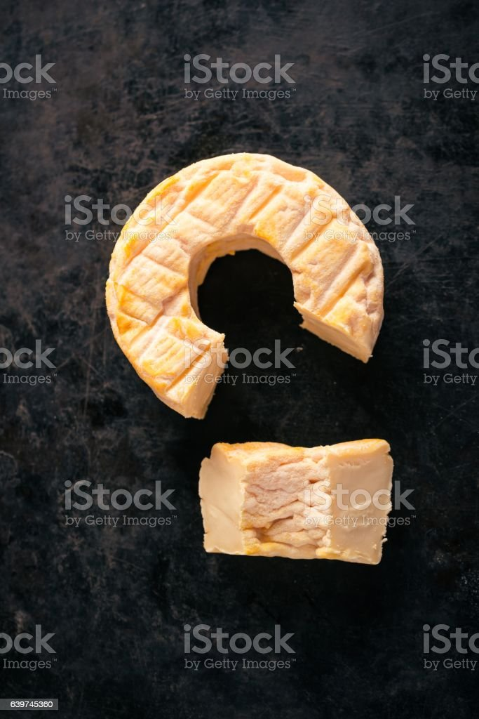 Top view on portion cut from whole golden camembert cheese stock photo