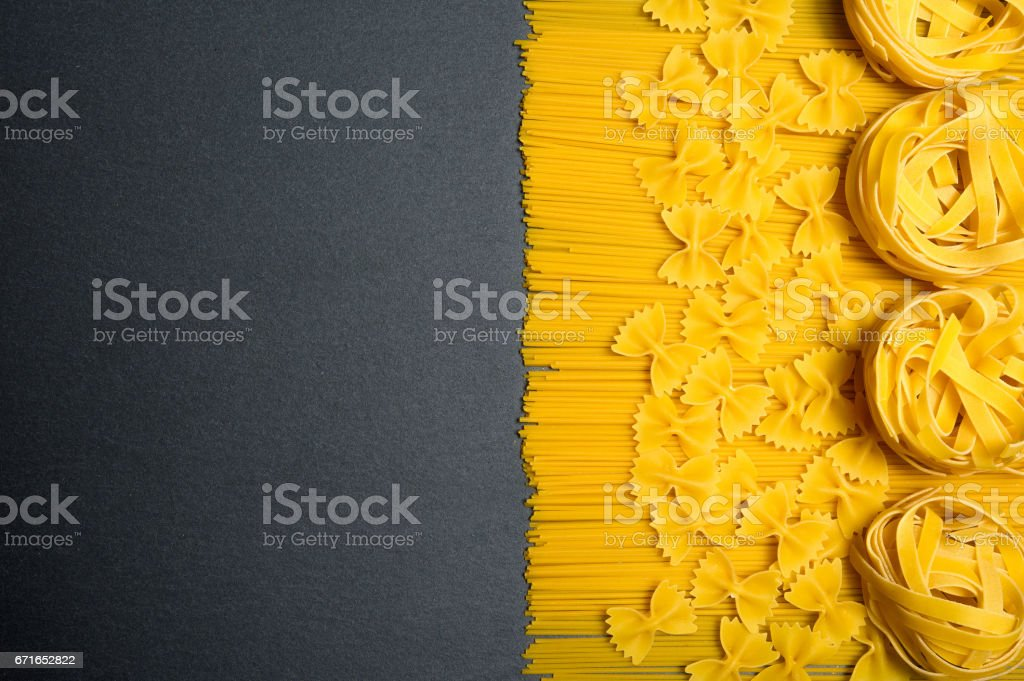 Top view: pasta on black stone slate background. Copy space stock photo
