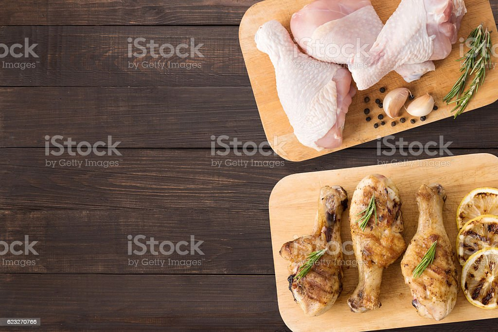 Top view raw chicken and grilled chicken on cutting board. stock photo