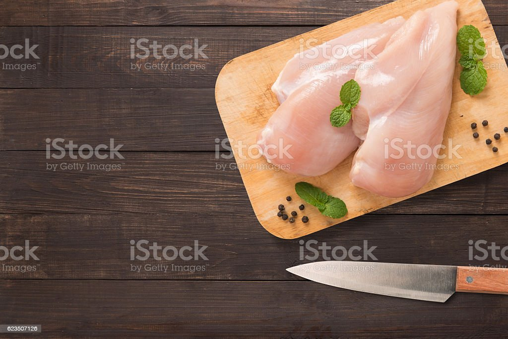 Top view raw chicken on cutting board on wooden. stock photo