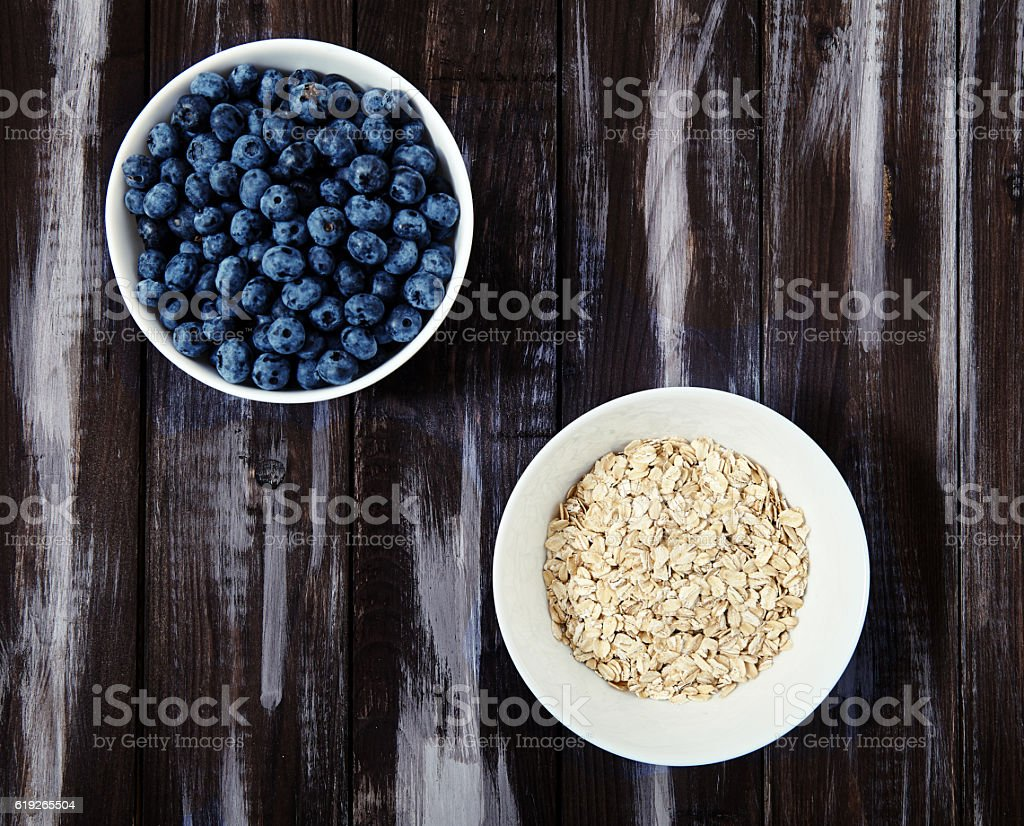 Top view shot of white bowls blueberries and oat flakes. stock photo