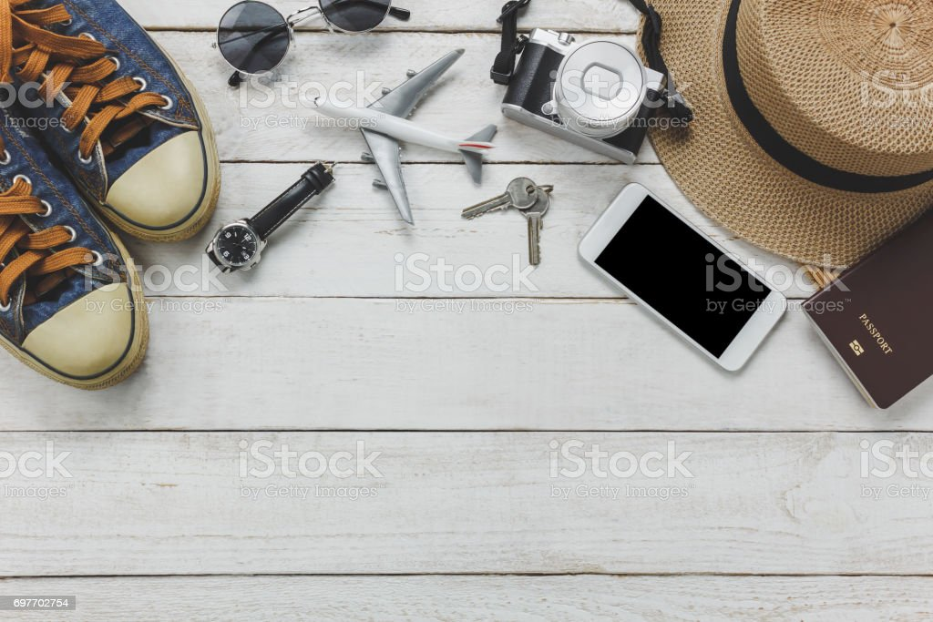 Top view women accessoires to travel concept.White mobile phone,airplane,hat,passport,watch,sunglasses on wood table. stock photo