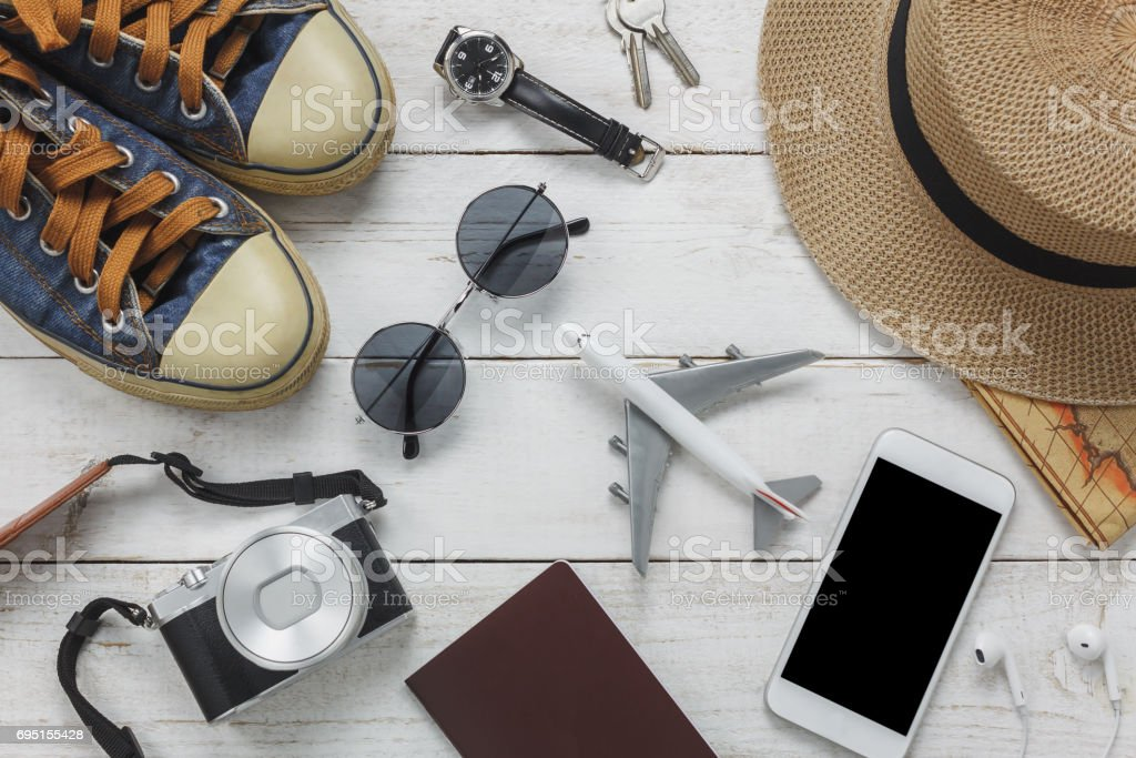 Top view women accessoires to travel concept.White mobile  phone and headphone on wooden background.airplane,hat,passport,watch,sunglasses on wood table. stock photo