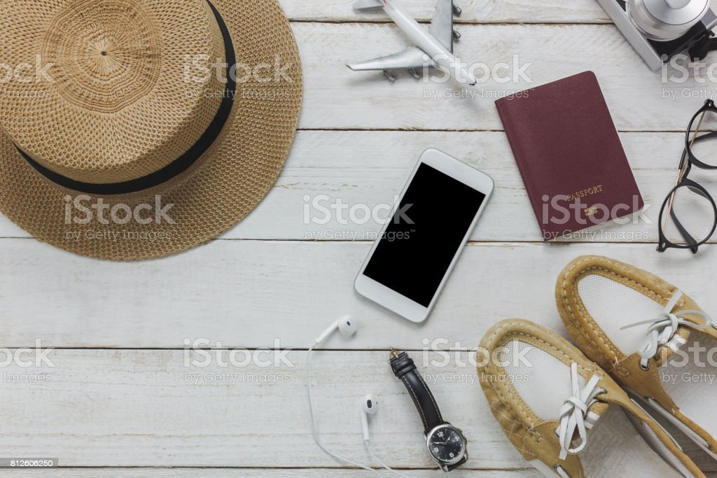 Top view women accessories to travel concept.White mobile phone,airplane,hat,passport,watch,eyeglasses on wood table. stock photo