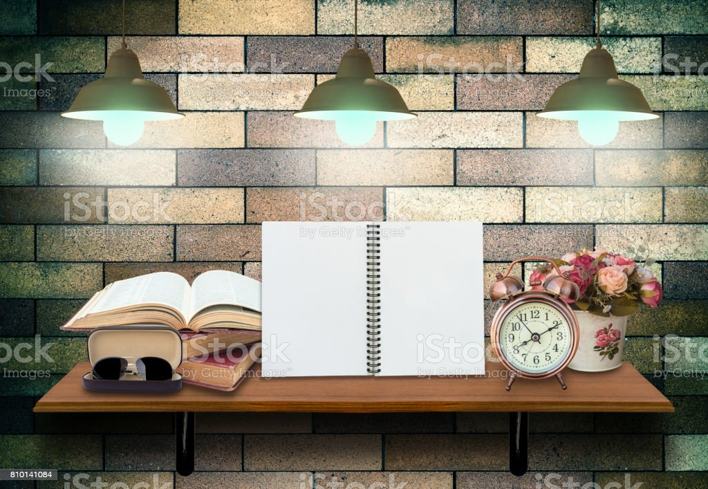 Top wooden shelves with empty netobook with open books, alarm clock and glasseson on the brick wall background with lighten .Product presentation concept stock photo