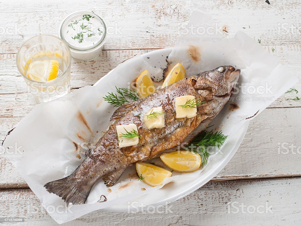Top-down shot of whole grilled fish with lemon slices stock photo