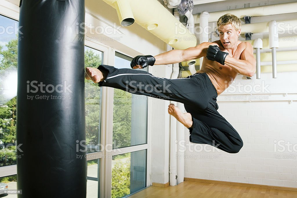 A topless man jumping up and kicking a heavy kicking bag stock photo