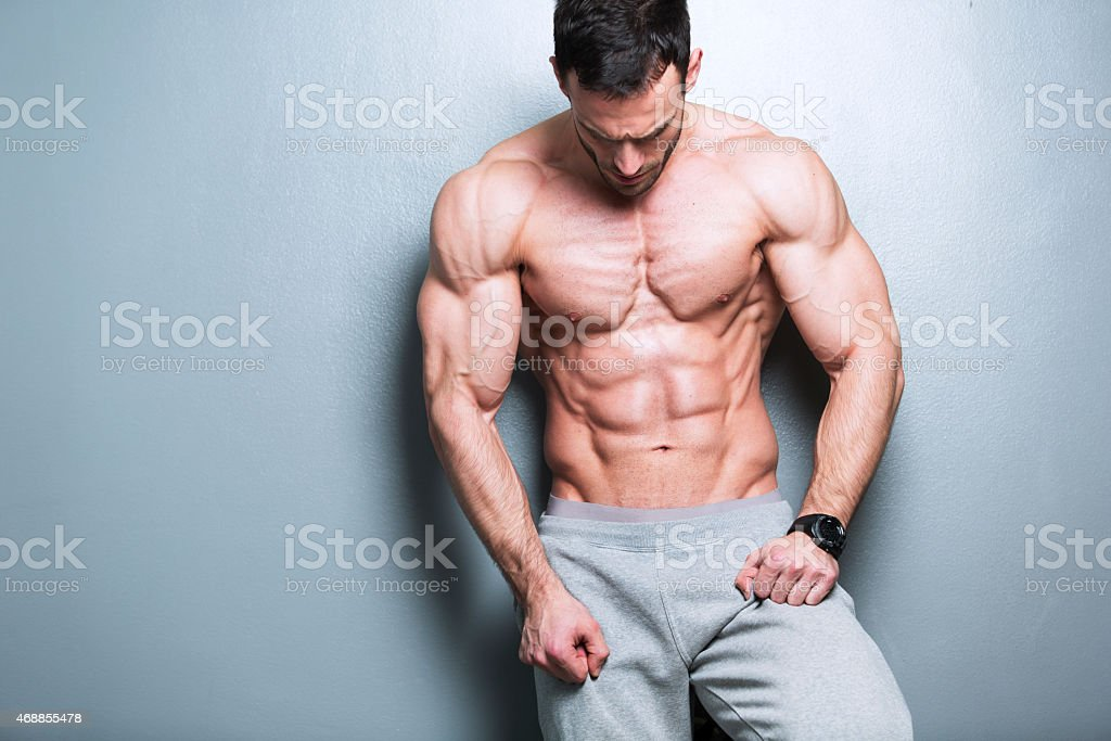 Topless muscular man leaning on a gray wall stock photo