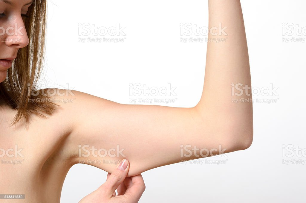 Topless solitary woman pinching bare arm stock photo