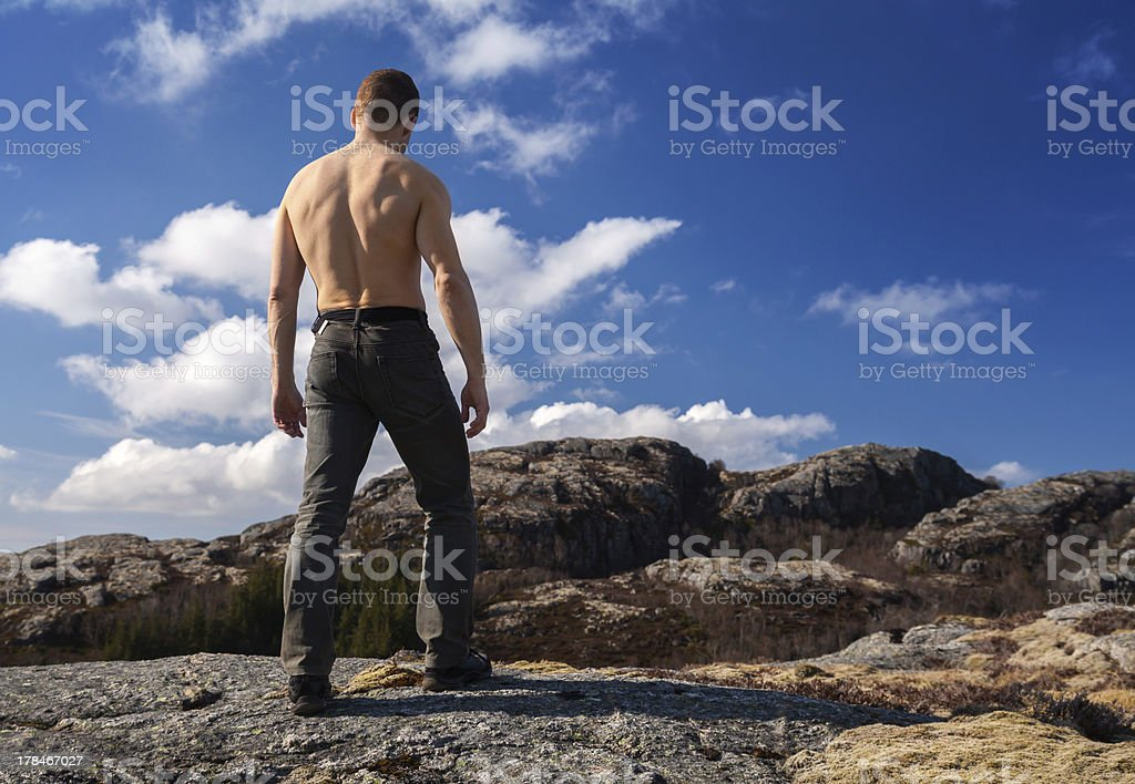 Topless strong man stands on the mountain and looks down royalty-free stock photo