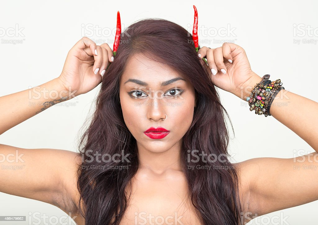 Topless woman using chili peppers to make horns stock photo