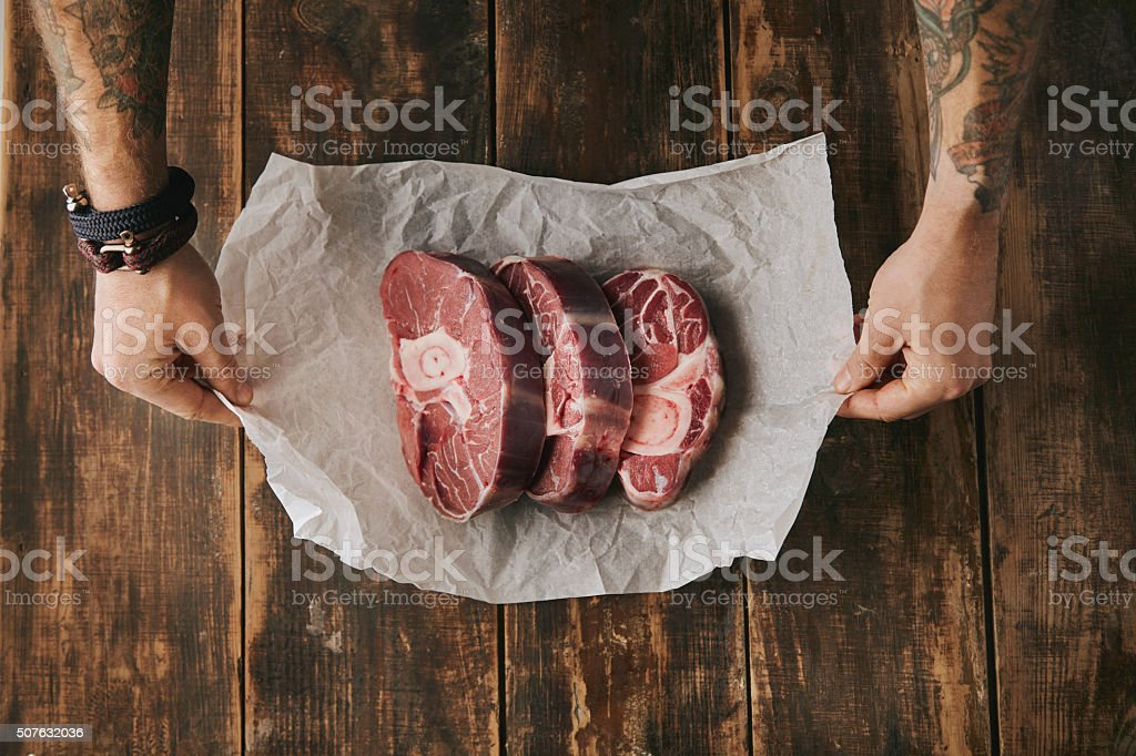 topview hands hold white paper three raw steaks stock photo