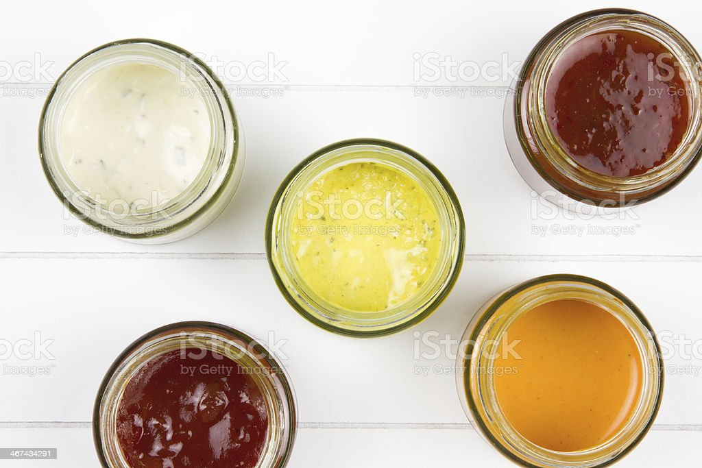 top-view of five jars filled with sauces stock photo