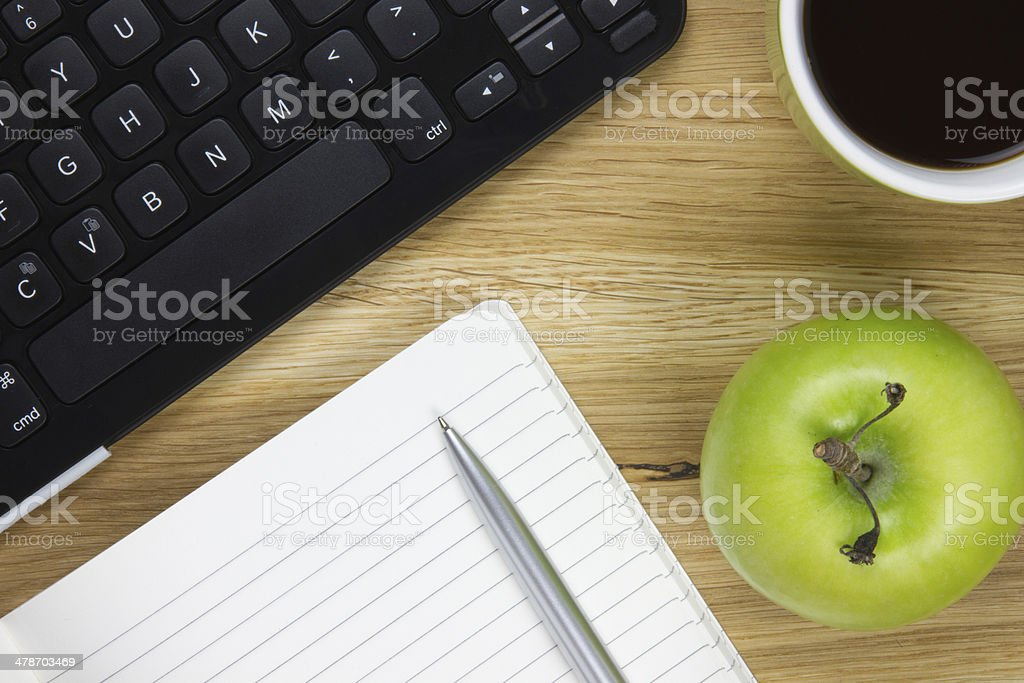 top-view of keyboard, apple and writing equipment stock photo