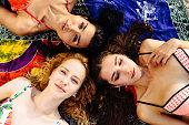 Topview of three beautiful slim mixed race girls in bikini