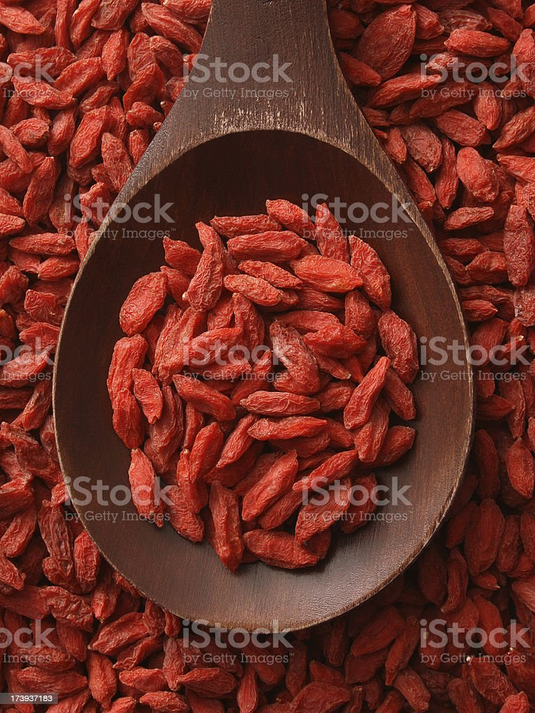 Top-view wooden spoon holding dried wolfberries stock photo