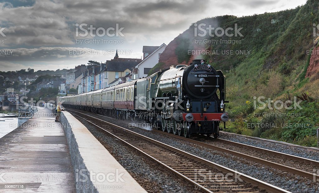Torbay Express steam train speeding past Dawlish with onlookers stock photo