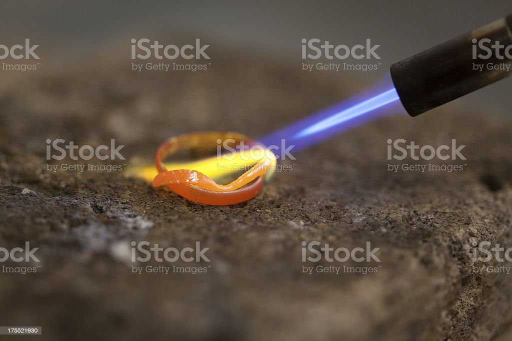 Torch melting a silver ring stock photo