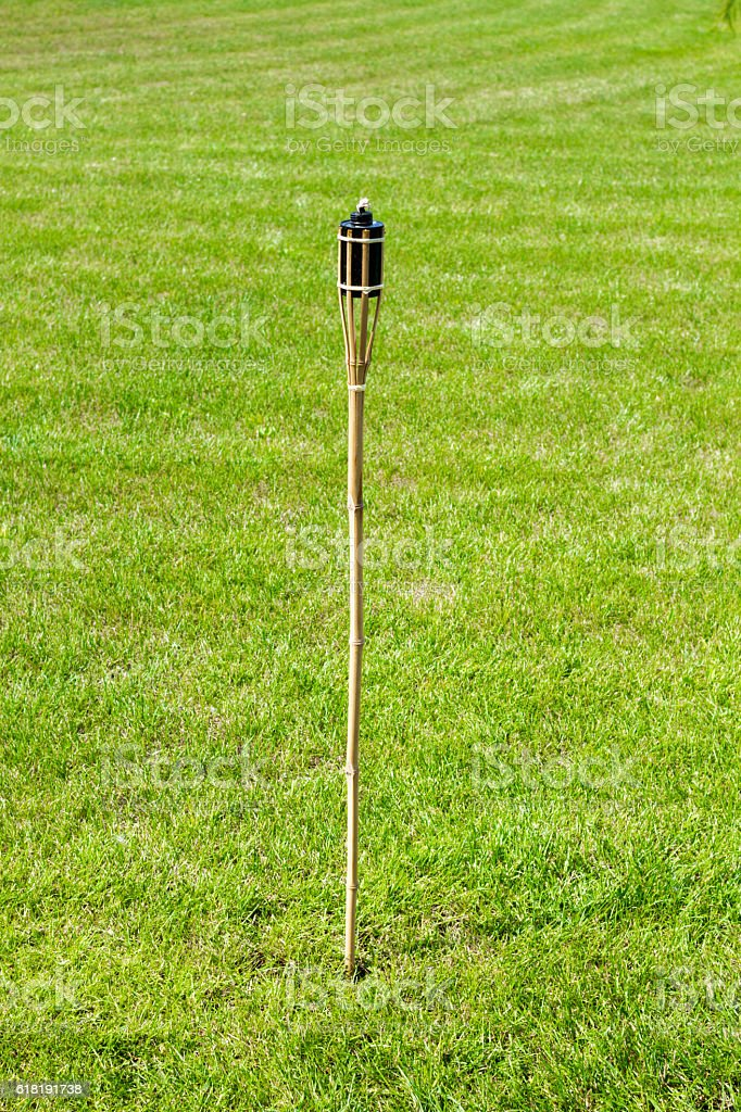 torch oil lamp on the grass field background stock photo