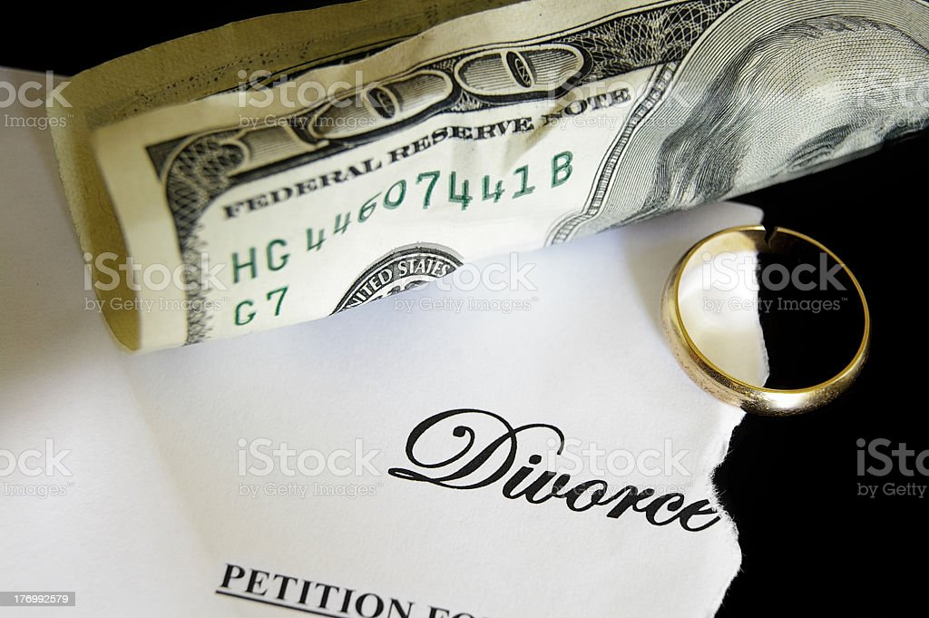 Torn divorce paper with a $100 bill and a gold ring royalty-free stock photo
