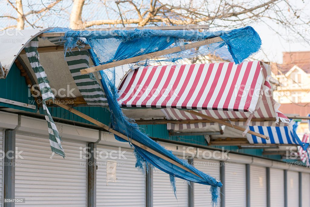Torn fabric awnings over closed seaside shops in the offseason stock photo