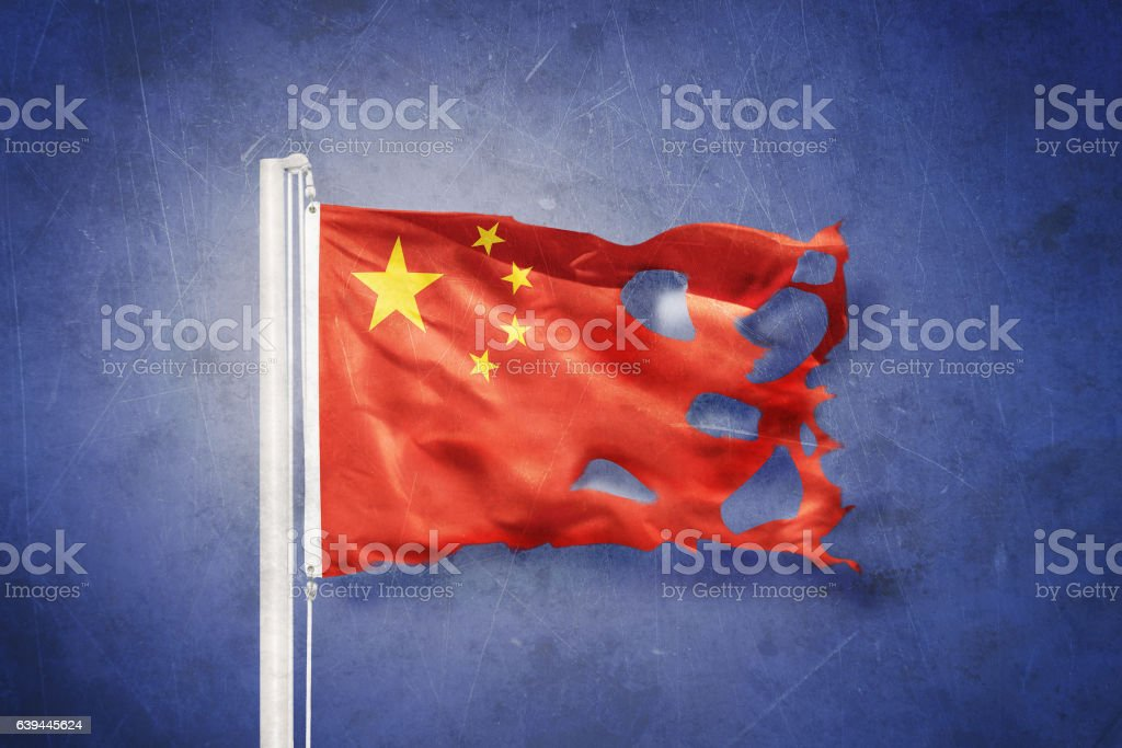 Torn flag of China flying against grunge background stock photo