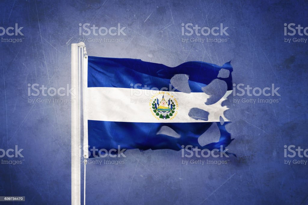 Torn flag of El Salvador flying against grunge background stock photo
