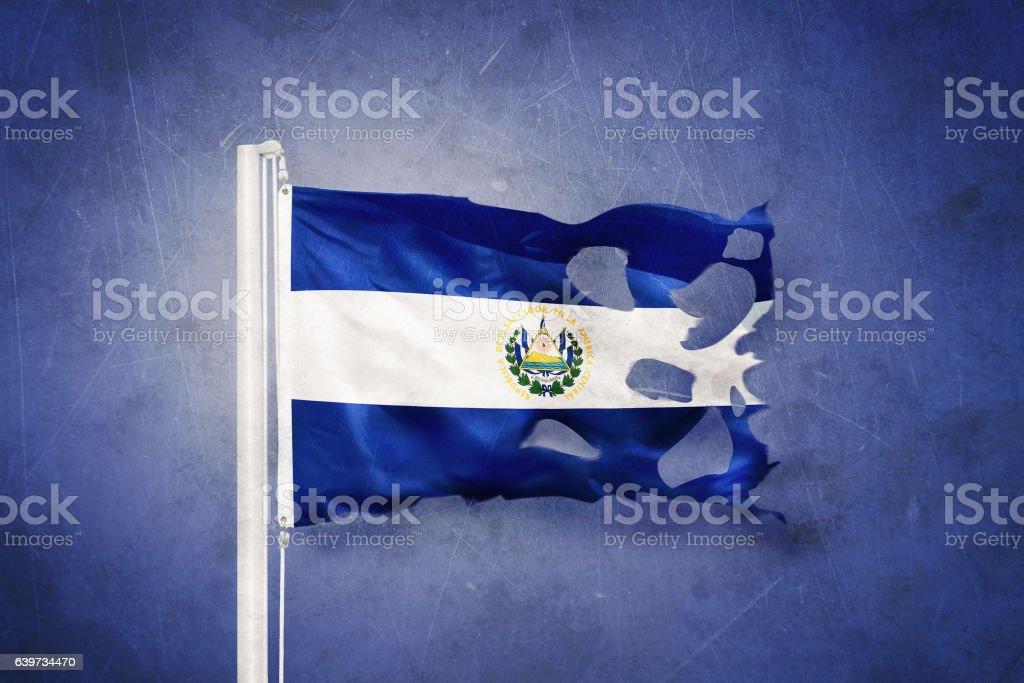 Torn flag of El Salvador flying against grunge background stock photo
