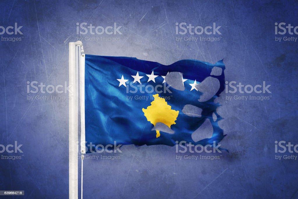 Torn flag of Kosovo flying against grunge background stock photo