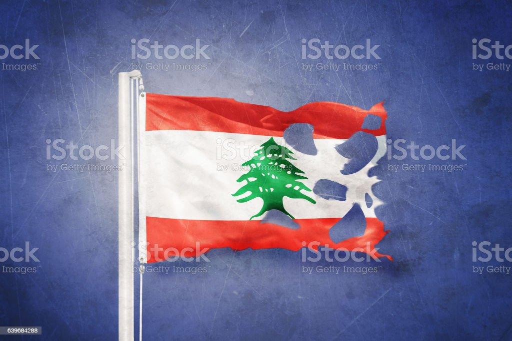 Torn flag of Lebanon flying against grunge background stock photo