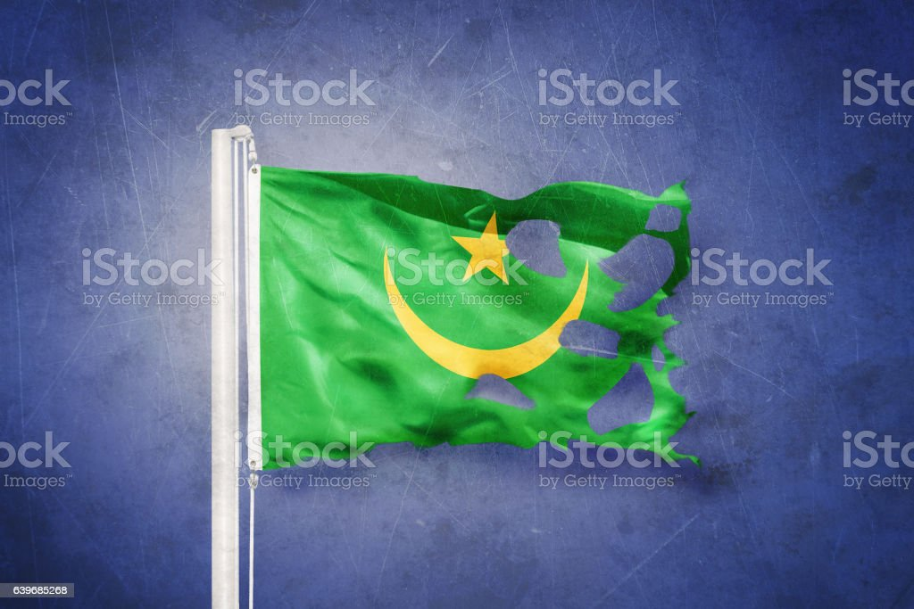 Torn flag of Mauritania flying against grunge background stock photo