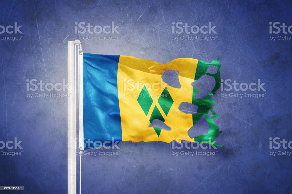 Torn flag of Saint Vincent and the Grenadines flying against stock photo